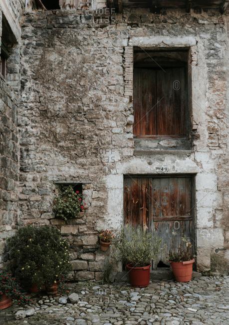 Yard with plant pots between grey rock old house with wood windows in Pyrenees