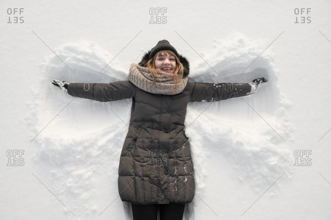 Woman in winter wear making snow angel