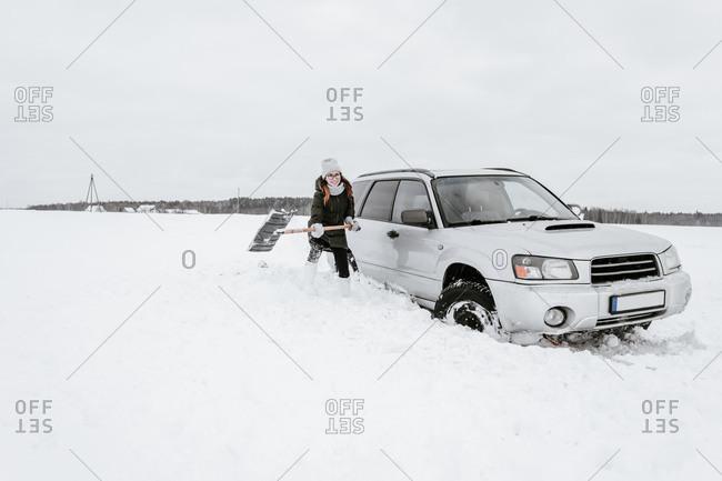 Woman with shovel near car on snow field