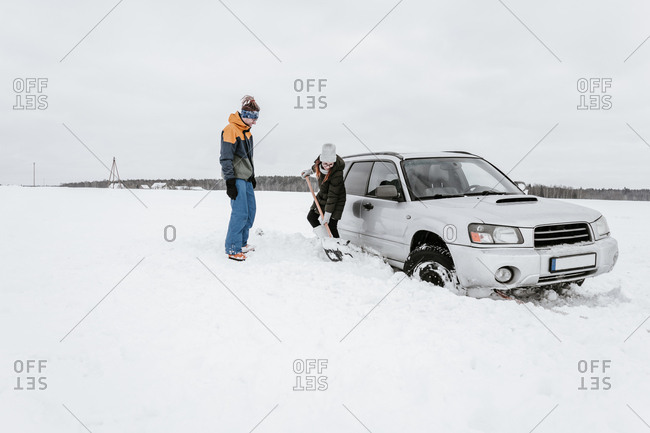 Woman with shovel near man and car on snow field