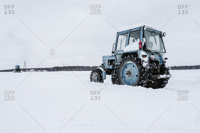 Tractors cleaning snow from field