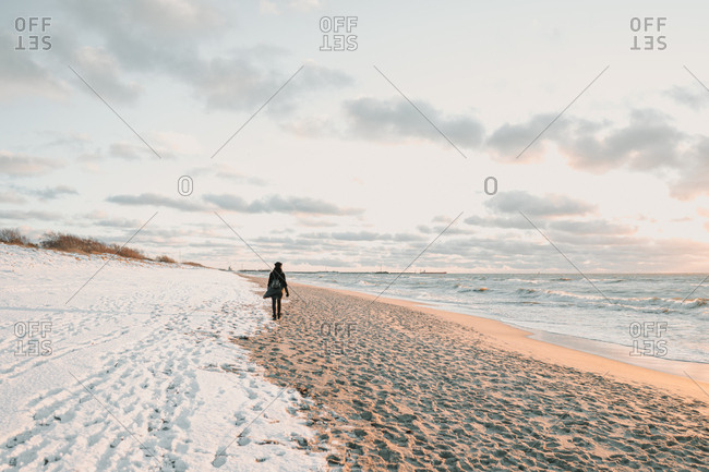 Woman walking on snow coast near sea