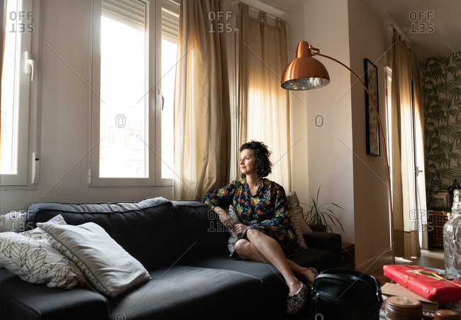 Young attractive lady in dress sitting on settee in apartment and looking through window