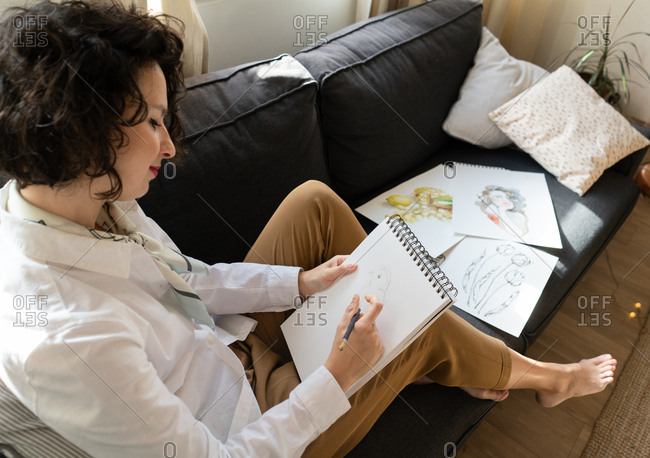 Woman writing on paper on sofa in room