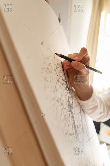 Person drawing city on canvas