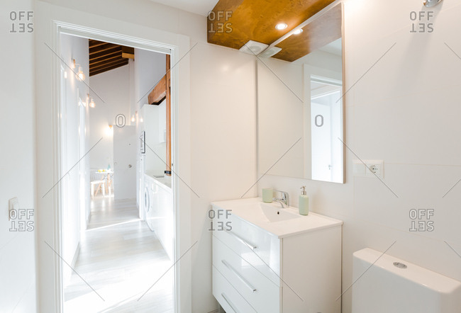 View of bathroom and kitchen in white flat in modern house