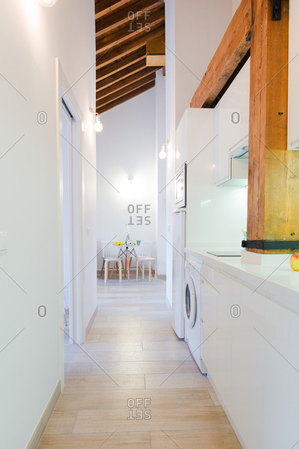 View of kitchen and table in white flat in modern house