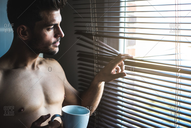 Thoughtful man standing by a windows blind with a cup of coffee