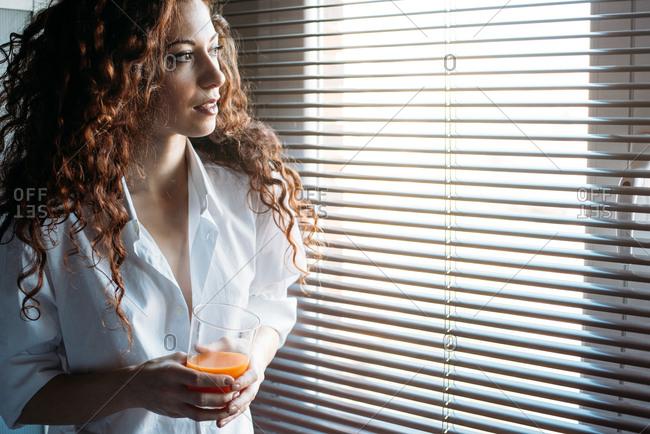 Beautiful woman standing by a windows blind drinking orange juice