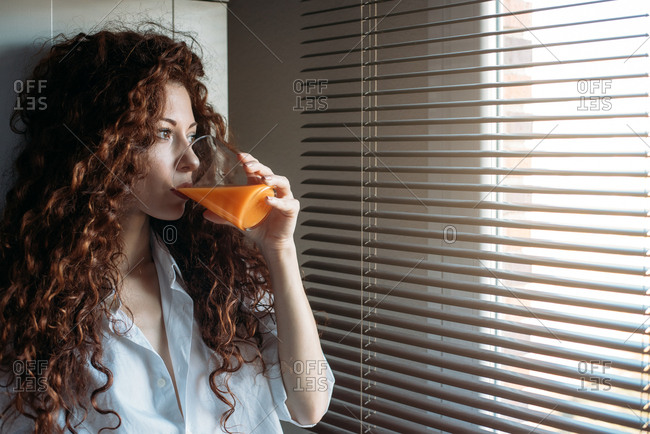 Beautiful woman standing by a windows blind drinking orange juice