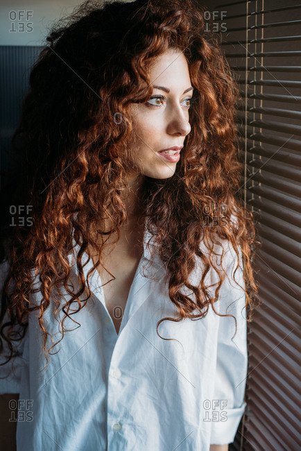 Beautiful thoughtful woman standing by a windows blind