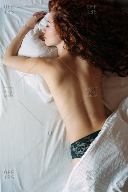Back view of a naked woman lying down in bed
