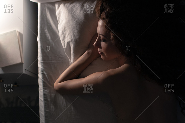 Back view of a naked woman lying down in bed at night