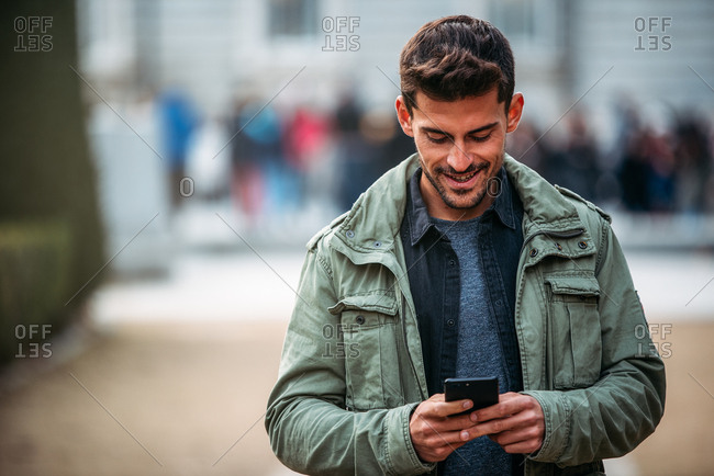 Young man on the mobile phone and walking in Madrid during winter