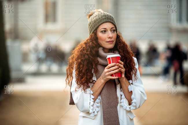 Young woman drinking coffee wandering in the streets of Madrid on winter