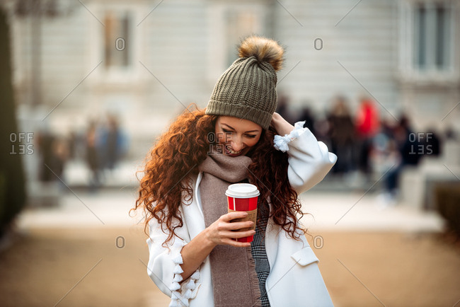 Cheerful woman drinking coffee wandering in the streets of Madrid on winter
