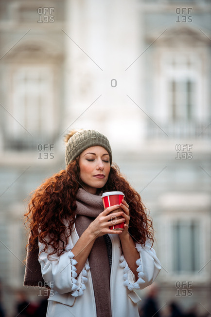 Young woman drinking coffee wandering in the streets of Madrid on winter with eyes closed