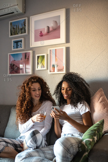Young cheerful women friends seating relaxed on the sofa with mobile phone in pajamas