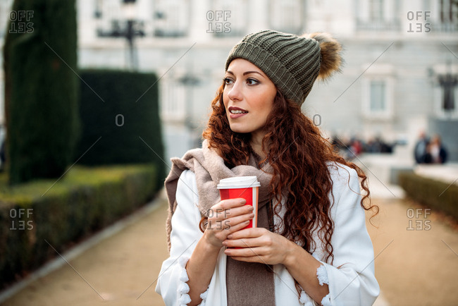 Young woman drinking coffee in the streets of Madrid on winter