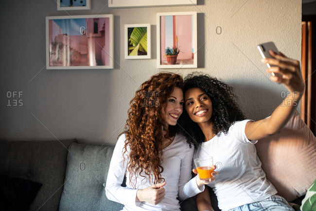 Young cheerful women friends seating relaxed on the sofa with mobile phone taking a selfie