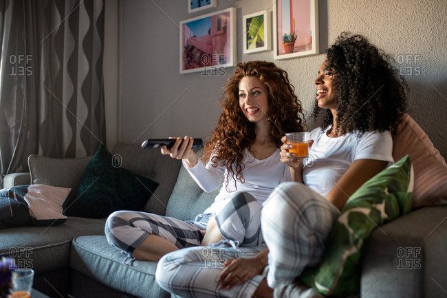 Young cheerful women friends seating on the sofa watching tv