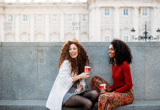 Two young women drinking coffee and talking in the streets of Madrid on winter