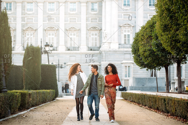 Three young friends walking in the streets of Madrid on winter