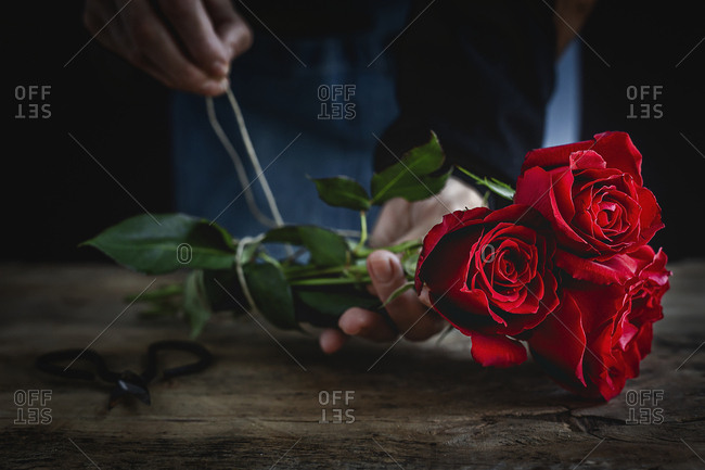 Unrecognizable woman making a bouquet of red roses for Valentine's Day. Love