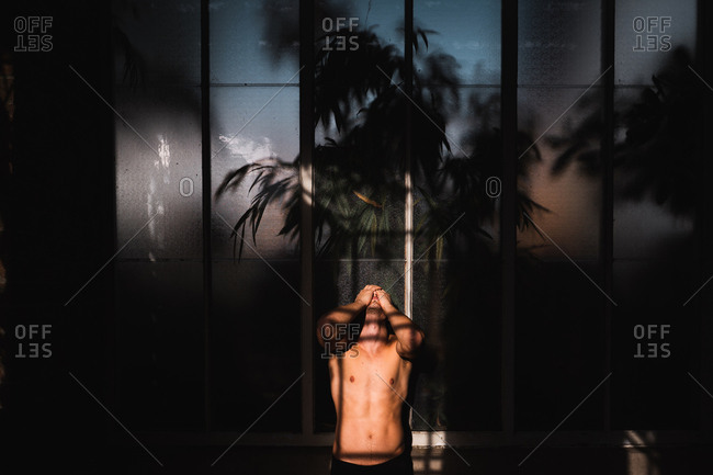 Young shirtless long haired guy looking upstairs and standing near facade of modern construction in Auckland, New Zealand