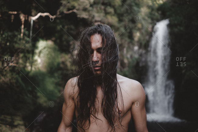 Handsome young man with long hair looking at camera and standing at cascade in Kaiate Falls, New Zealand