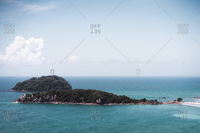 View to small green islands in blue calm ocean at Mount Maunganui, New Zealand