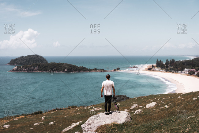 Back view of man in hat standing on coast and looking on calm ocean and small green islands at Mount Maunganui, New Zealand