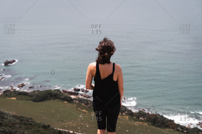 Back view of woman standing high and looking at calm blue ocean from Mount Maunganui, New Zealand