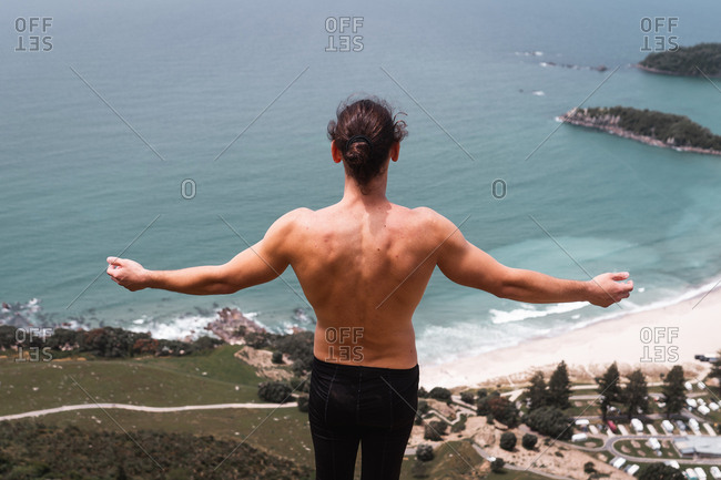 Back view of shirtless man standing on top of the mountain and looking at ocean from Maunganui, New Zealand