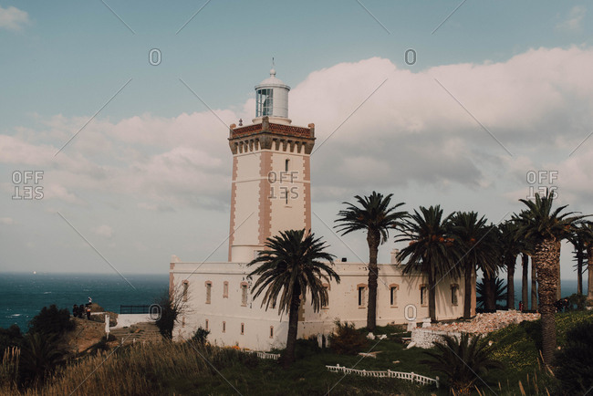 Beautiful aged lighthouse near tropical trees, sea and cloudy sky in Chefchaouen, Morocco