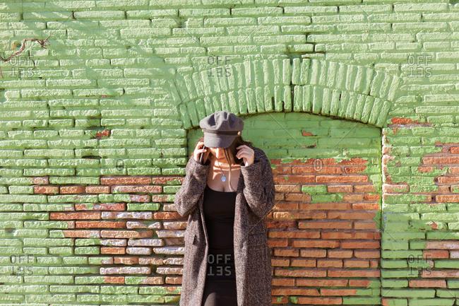Charming Hispanic lady talking phone near wall