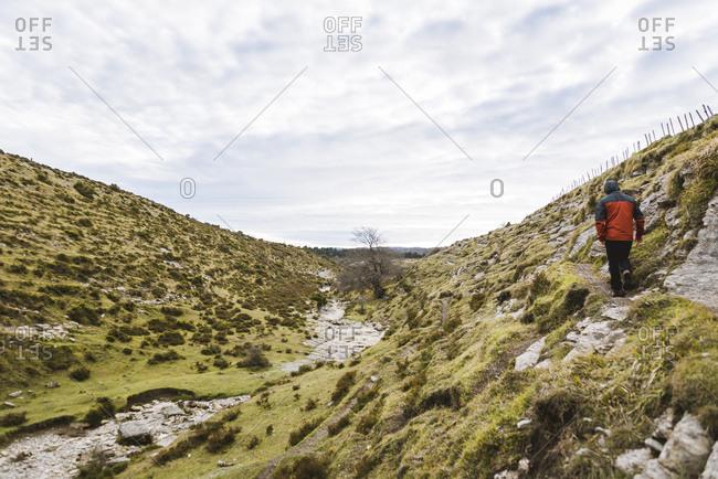 Man walking on hill near valley