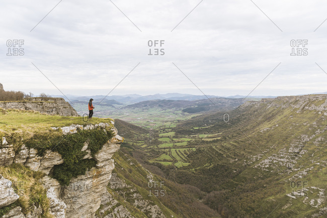Side view of guy in coat standing on top of high mountain near valley with green plants and cloudy sky