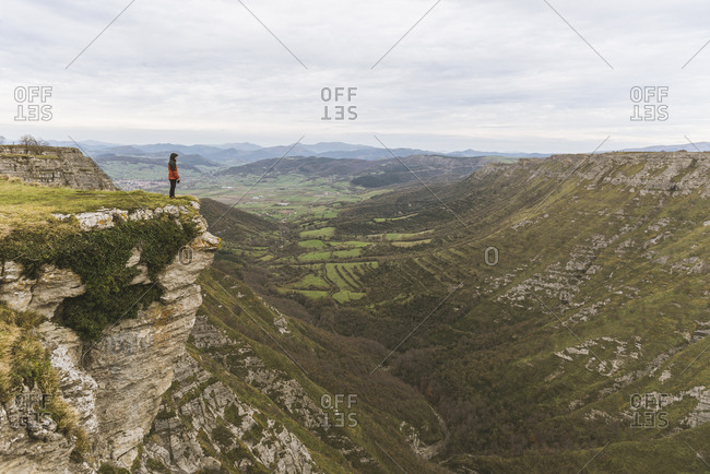 Man standing on cliff near valley