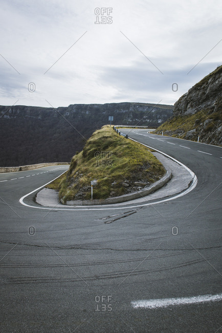 Asphalt route running between hills and cloudy sky with sun