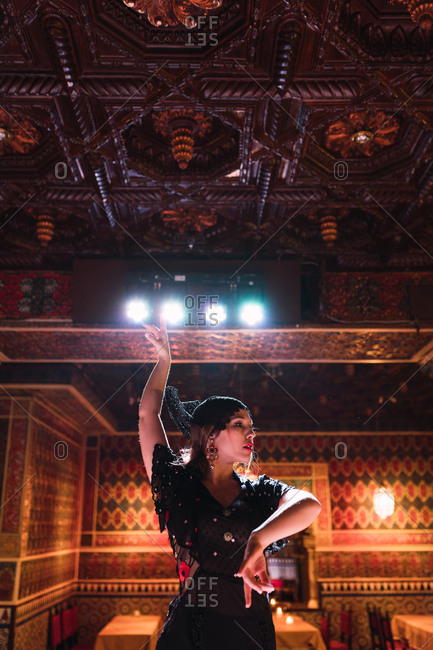 Young lady in dress dancing flamenco on scene in luxury oriental room decorated by mosaic
