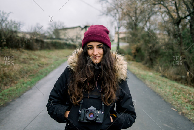 Attractive young cheerful lady in winter wear and hat with camera and hands in pockets on countryside road in Orduna, Spain