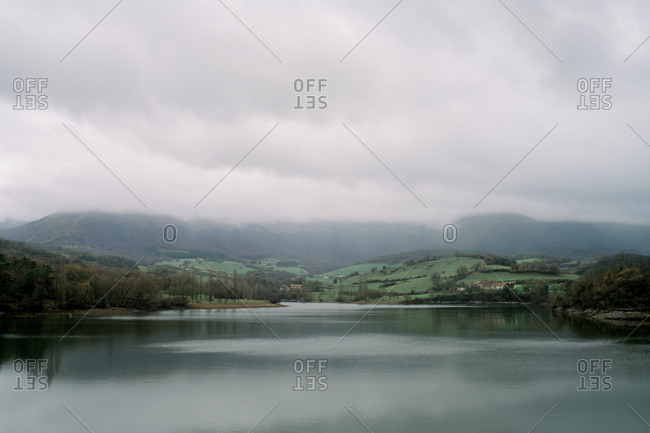 Picturesque view of lake between plants and mountains in rainy weather in Orduna, Spain