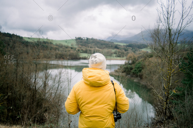 Back view of human in yellow coat and hat with camera looking at picturesque view of lake between hills in Orduna, Spain