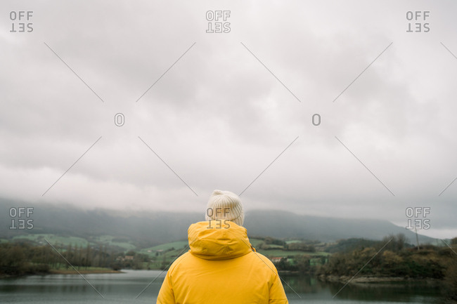 Person in coat with camera near lake