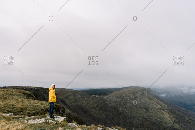 Side view of guy in yellow coat and hat standing on top of mountain and cloudy sky in Orduna, Spain