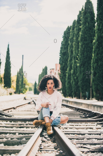 African-American woman sitting in the tracks of a train