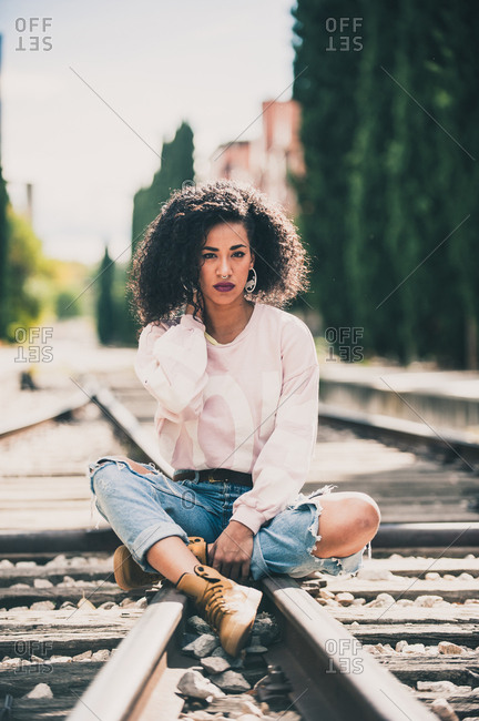 African-American woman looking at camera in the tracks of a train