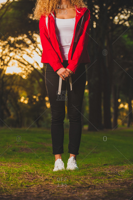 Crop sportive woman standing on meadow