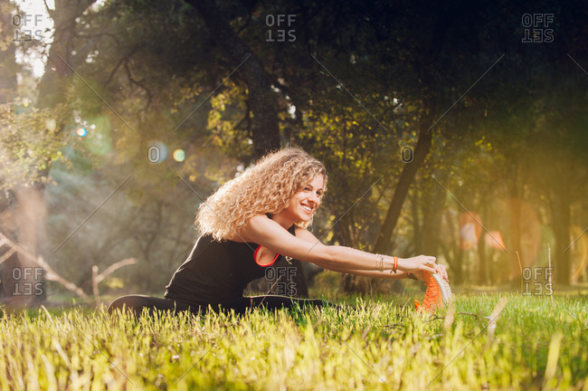 Happy woman stretching on sunny meadow